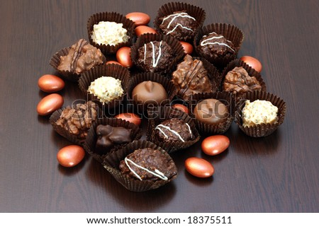 chocolates isolated on brown background - stock photo