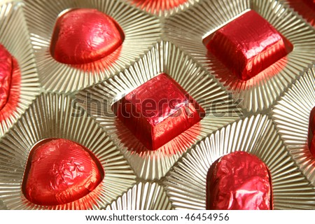 Chocolates wrapped in red paper lie in a box. View from the top - stock photo