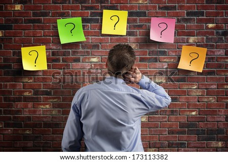 Choice and decisions: businessman thinking with question marks written on adhesive notes stuck to a brick wall - stock photo