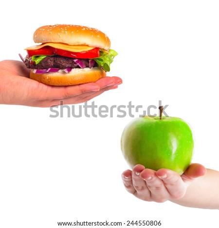 Choice between healthy apple and unhealthy hamburger - stock photo