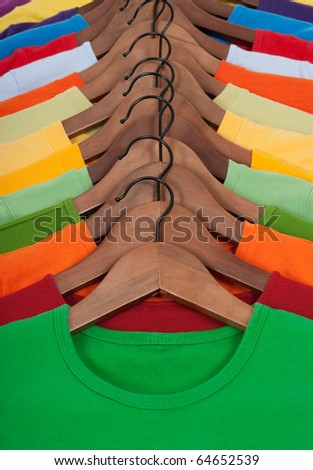 Choice of vibrant colorful t-shirts on wooden hangers. - stock photo