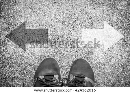 choices concept - feet on floor with direction arrows (black and white) - stock photo