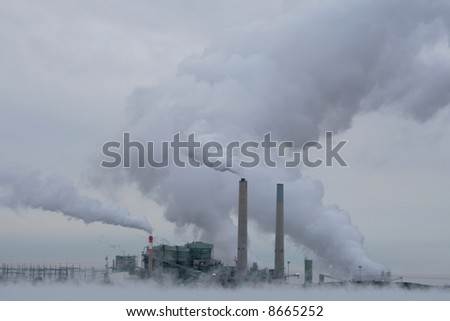 Cholla coal-fired power plant produces smoke and steam on a cold cloudy - stock photo