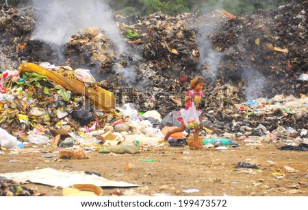Chonburi, Thailand -  July 2013 - An unidentified girl on Sichang island runs around the huge trash heap where all wasteful stuffs and rotten food are compiled here for garbage disposal  - stock photo