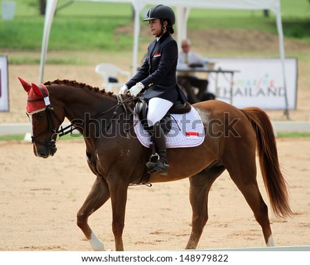 CHONBURI, THAILAND - JULY 26:Pingkan Motira of Indonesia with Fluck in action during 1st FEI Asian Eventing Championships 2013 at Thai Polo&Equestrian Club on July 26, 2013 in Chonburi, Thailand. - stock photo