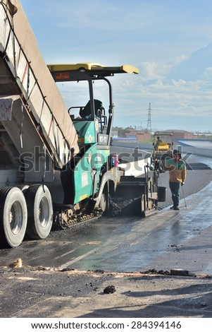 CHONBURI, THAILAND - MAY 21, 2015 : Worker operating the asphalt paver machine at road construction site.