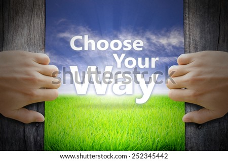 Choose your way motivational quotes. Hand opening an old wooden door and found a texts floating over green field and bright blue Sky Sunrise. - stock photo