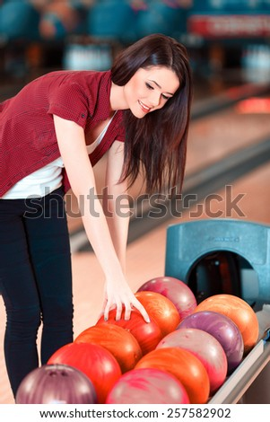 Choosing a ball. Cheerful young women choosing bowling ball and smiling while standing against bowling alleys - stock photo