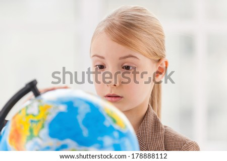 Choosing a place to travel. Concentrated little girl in formalwear examining globe with a loupe while sitting at the table - stock photo