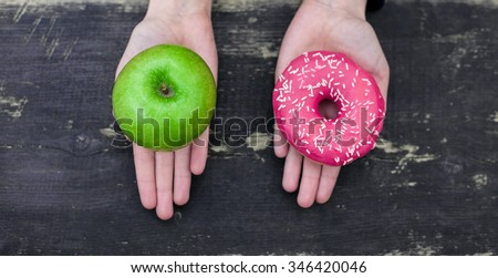 Choosing between apple and donut - stock photo