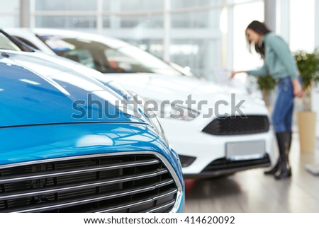 Choosing carefully. Selective focus on a brand new car at the car salon woman choosing a car on the background - stock photo