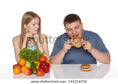 Choosing healthy eating concept. Surprised woman looking her boyfriend eating fast food, against white background