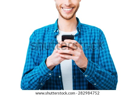 Choosing right words. Close-up of young man in shirt holding mobile phone and smiling while standing against white background