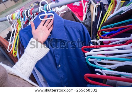 Choosing  second hand clothes - stock photo