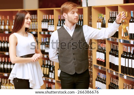 Choosing the best wine for you. Cheerful young sommelier holding a wine bottle and pointing it  - stock photo