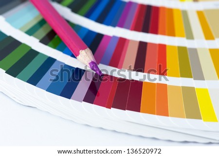 choosing the color from the spectrum - open pantone color card with pink pencil - stock photo