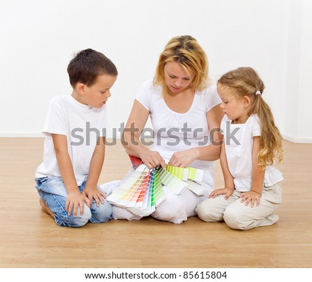Choosing the colors in our new home - woman and kids with color chart - stock photo