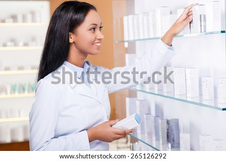 Choosing the right medicine for you. Beautiful young African woman in lab coat choosing medicine while standing near the self in drugstore  - stock photo