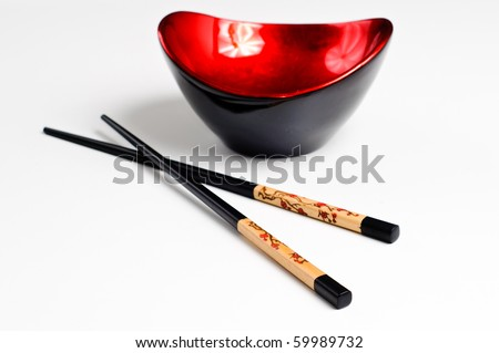 Chop sticks and a red bowl - stock photo