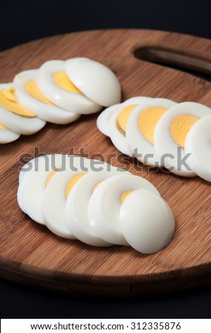 Chopped and boiled eggs arranged on a kitchen wooden board on the black background. - stock photo