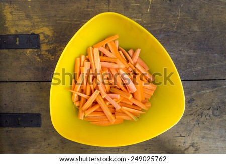 Chopped carrots in yellow bowl on wooden desk