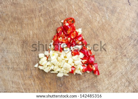 Chopped chili pepper and garlic on the wooden chopping block - stock photo