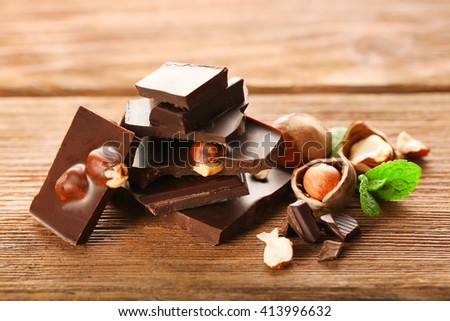 Chopped chocolate bar  with mint and hazelnuts on wooden table. - stock photo
