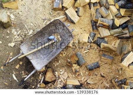 Chopped firewood next to wheelbarrow and axe - stock photo