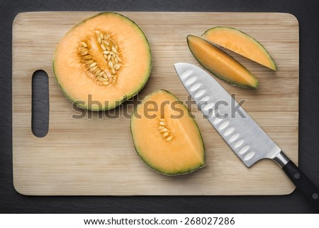 Chopped fresh musk melon on a cutting board on grey slate background, looking fresh and healthy. - stock photo