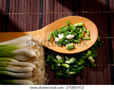 Chopped green  onions and spoon on a wooden - stock photo