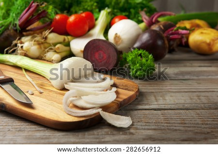 Chopped green onions on a chopping board on a wooden table. next to the green onions are young homegrown vegetables. beets, onions, potatoes, parsley, cherry tomatoes. rustic style - stock photo