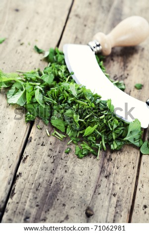 chopped herbs on cutting board with a mezzaluna - stock photo