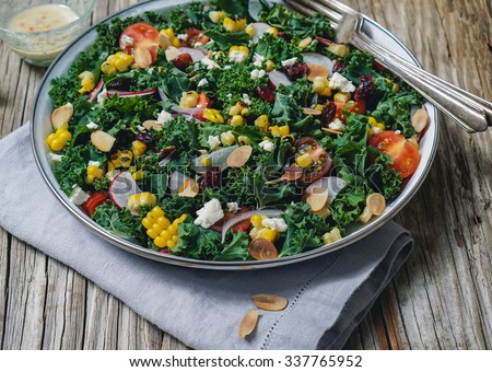 Chopped kale, grilled corn, tomatoes, dried cranberries and nuts salad on wood background/ Selective focus - stock photo