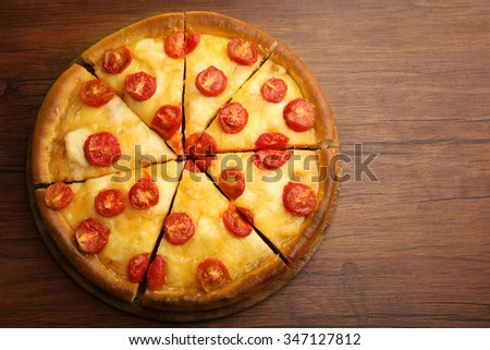 Chopped Margherita pizza on wooden table - stock photo
