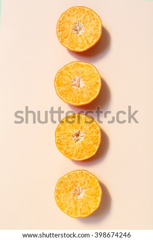 Chopped orange isolated on pink background - stock photo