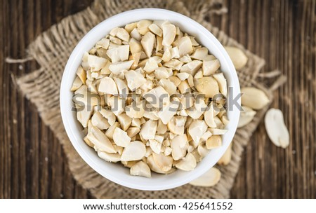 Chopped Peanuts (close-up shot; selective focus) on wooden background - stock photo