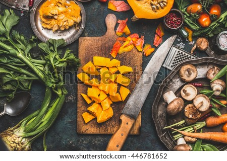 Chopped Pumpkin on rustic cutting board with kitchen knife and mushrooms and vegetables ingredients  for tasty vegetarian cooking, dark styled,  top view - stock photo