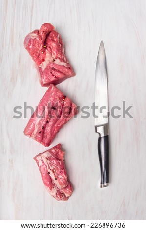 chopped raw pork fillet with meat knife on white wooden background, top view - stock photo