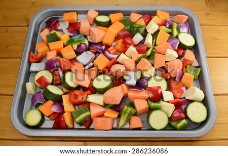 Chopped raw vegetables - red onion, butternut squash, red pepper, courgette, parsnip, green pepper, sweet potato - suitable for roasting - stock photo