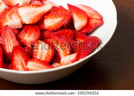 Chopped strawberries in a white bowl over a wooden background - stock photo