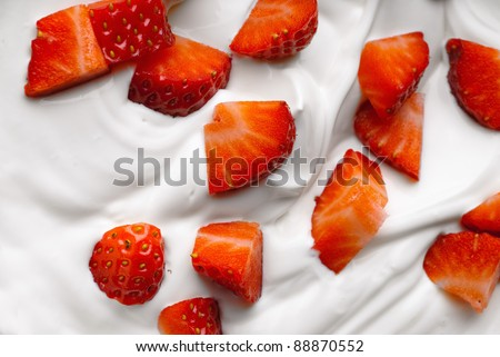 Chopped strawberry in a bowl of whipped cream - stock photo