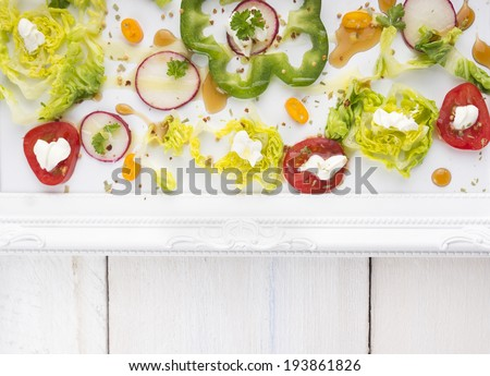 Chopped summer vegetables in tray with patterned border on white wooden table , top view - stock photo