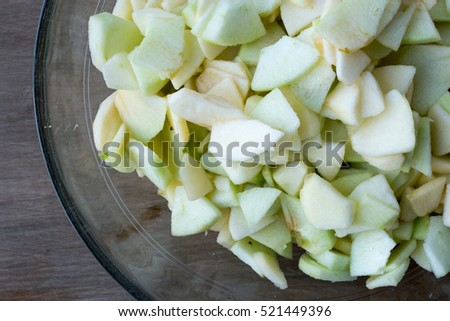 Chopped up green apples in a bow.