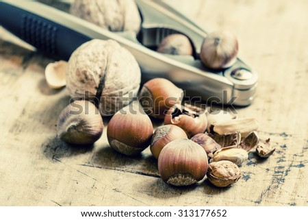 Chopped walnuts, hazelnuts and pistachios with tongs for splitting on a wooden background, selective focus - stock photo