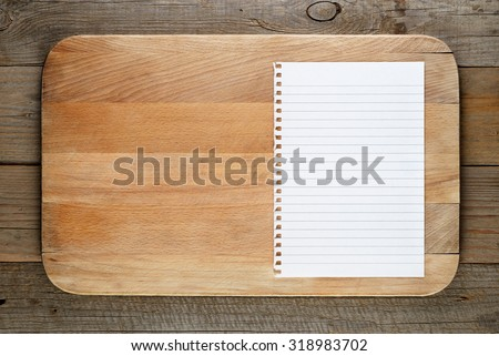 Chopping board and paper for recipe on wooden background