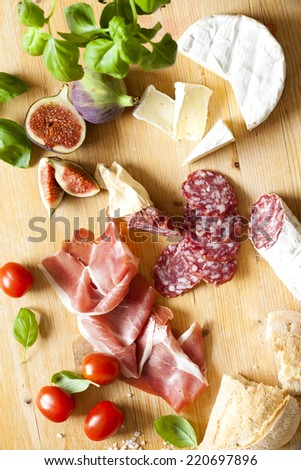 Chopping board of Assorted Cured Meats and Cheese - stock photo