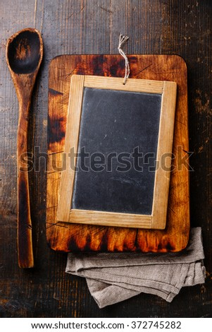 Chopping board, old wooden spoon and Vintage slate chalk board on dark wooden background - stock photo