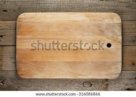 Chopping board on wooden background - stock photo