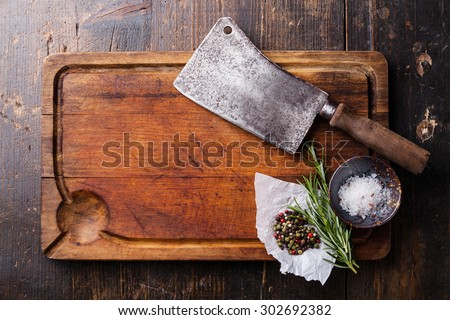 Chopping board, seasonings and meat cleaver on dark wooden background - stock photo