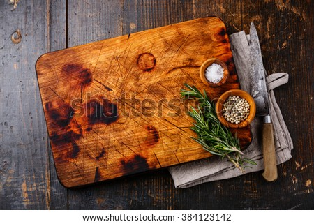 Chopping cutting board, salt, pepper and rosemary with kitchen knife on dark wooden background - stock photo